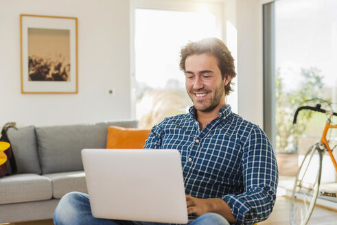 Portrait of smiling young man sitting in the living room using laptop - UUF006496