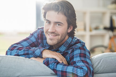 Portrait of smiling man with brown hair leaning on backrest of couch - UUF006517