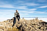 Bolivia, Atacama, Altiplano, Salar de Uyuni, man sitting on stone - GEMF000700