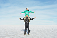 Bolivia, Salar de Uyuni, couple, woman sitting on shoulders of man - GEMF000712