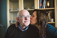 Senior woman kissing her husband at home - RAEF000854