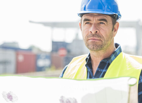 Man wearing hard hat holding document at container port - UUF006522