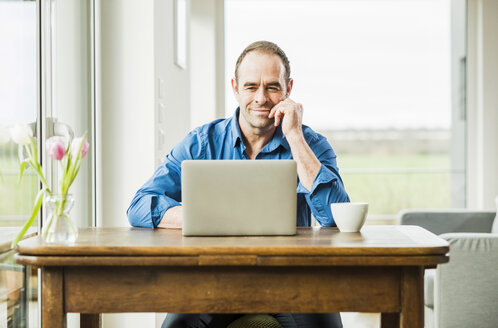 Businessman at home with laptop at wooden table - UUF006540