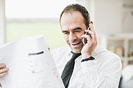 Businessman holding plan and talking on cell phone - UUF006549