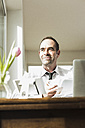 Confident businessman at wooden table thinking - UUF006552