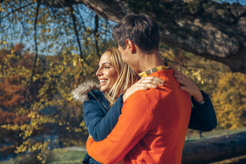 Happy couple embracing in autumn forest - CHAF001569