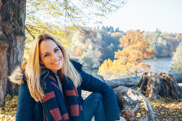 Smiling woman enjoying autumn in a forest sitting on a trunk - CHAF001578