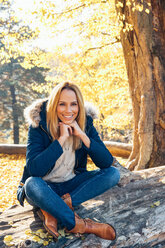 Smiling woman enjoying autumn in a forest sitting on a trunk - CHAF001581
