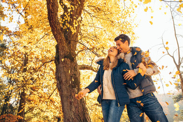 Happy couple having fun in autumn in a forest - CHAF001587