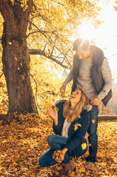 Happy couple having fun in autumn in a forest - CHAF001590