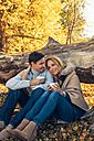 Smiling couple holding cups in autumn forest - CHAF001593