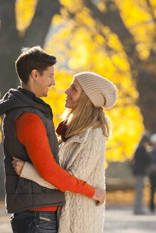 Happy couple embracing in autumn forest - CHAF001596