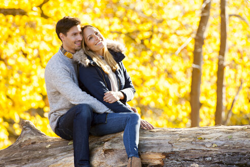 Happy couple enjoying autumn in a forest sitting on a trunk - CHAF001611