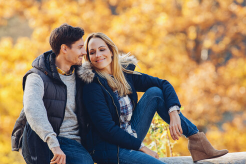 Happy couple enjoying autumn in a forest sitting on a trunk - CHAF001617