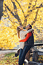 Happy couple enjoying autumn in a park - CHAF001632