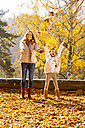 Mother and her little daughter throwing autumn leaves into the air - CHAF001641