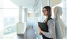 Young woman with black file standing at corridor of an office - MGOF001338