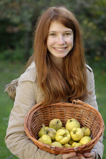 Portrait of smiling girl holding wickerbasket with quinces - LBF001367