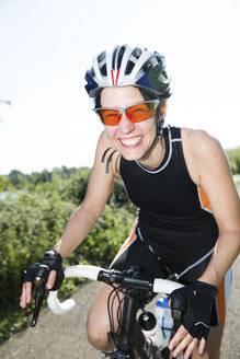 Portrait of happy racing cyclist wearing sunglasses and cycling helmet - JATF000836