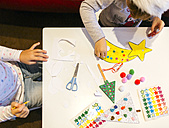 Two little girls tinkering Christmas decoration - MGOF001355