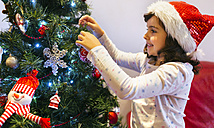 Happy little girl with Christmas hat decorating Christmas tree - MGOF001364