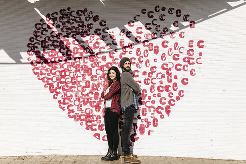 Young couple standing back to back in front of a brick wall with a heart - JRFF000404