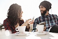 Young couple talking at a street cafe - JRFF000410