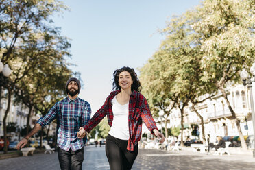 Spain, Tarragona, happy young couple running in the city - JRFF000413