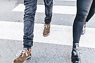 Legs of man and woman walking on crosswalk - JRFF000419