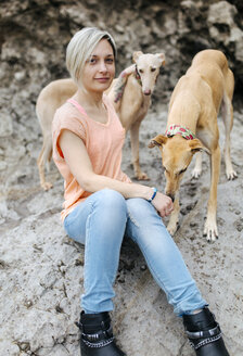 Spain, Llanes, portrait of young woman with her greyhounds on the beach - MGOF001374