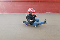 Little boy with safety helmet sitting on a skateboard - VABF000136