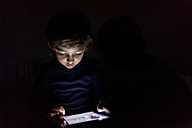 Little boy in darkness playing with digital tablet - VABF000139