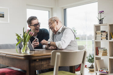 Senior man and his grandson sitting at table in the living room with laptop and smartphone - UUF006565