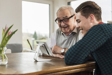 Happy senior man and his grandson looking at mini tablet - UUF006574