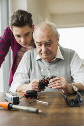 Portrait of senior man and grandson with toy train at home - UUF006586