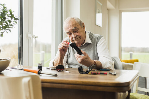 Senior man repairing toy train at home - UUF006589