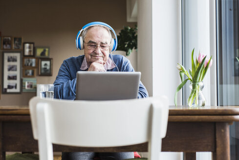 Senior man using laptop and headphones at home - UUF006610