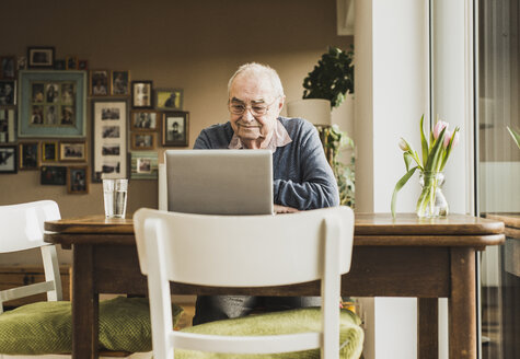 Senior man sitting at table in the living room using laptop - UUF006613