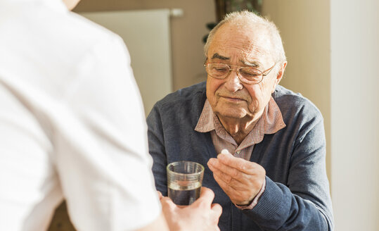 Senior man getting tablet and glass of water - UUF006619