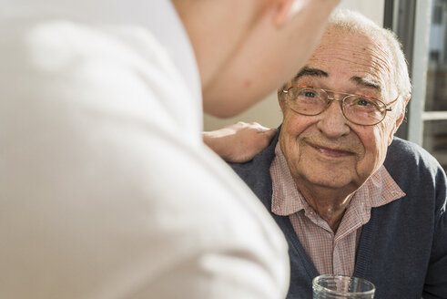 Portrait of smiling senior man face to face with his geriatric nurse - UUF006622