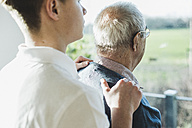 Back view of senior man and his  geriatric nurse - UUF006625