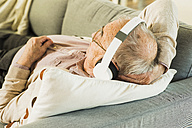 Senior man lying on the couch hearing music with headphones - UUF006628