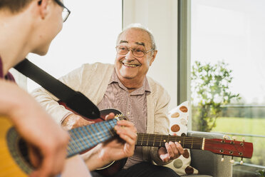 Portrait of senior man playing guitar with his grandson - UUF006631