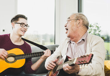 Senior man singing and playing guitar with his grandson - UUF006634
