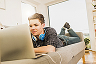 Young man lying on couch using laptop - UUF006640