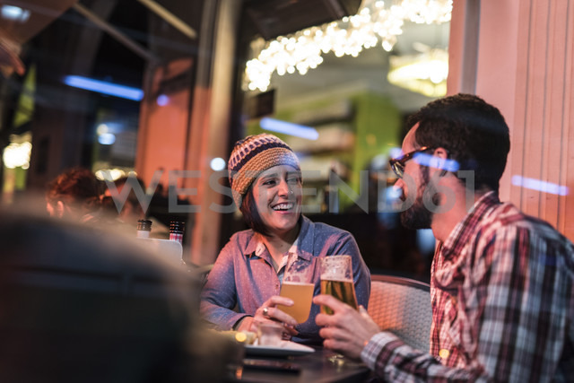 Couple drinking beer in a winter terrace bar behind a glass - JASF000378