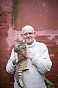 Portrait of senior man holding tabby cat - RAEF000861