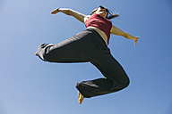 Jumping woman in front of blue sky - ABZF000196