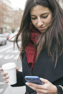 Spain, young woman with coffee to go looking at her smartphone - ABZF000198
