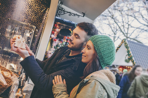Couple looking at handmade wooden decoration on the Christmas Market - MF002649